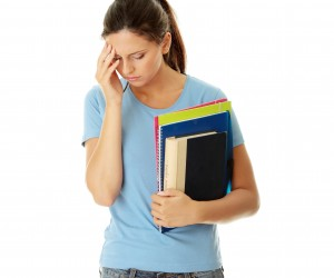 teen girl holding books with hand on head