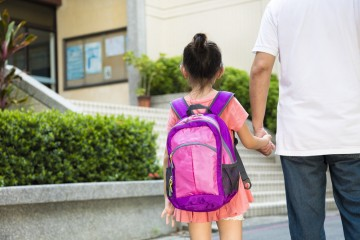 parent and girl walking into school