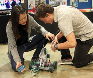 a female and male student work on a robotic vehicle while both are hunched over it