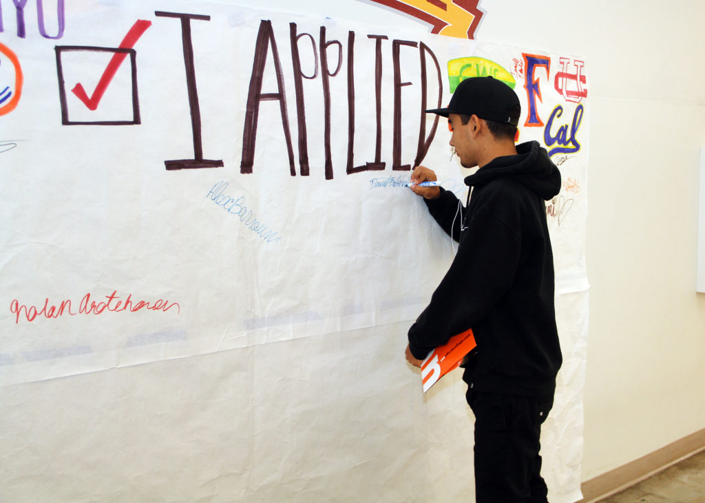 """Student signing a banner that reads, """"I applied."""""""
