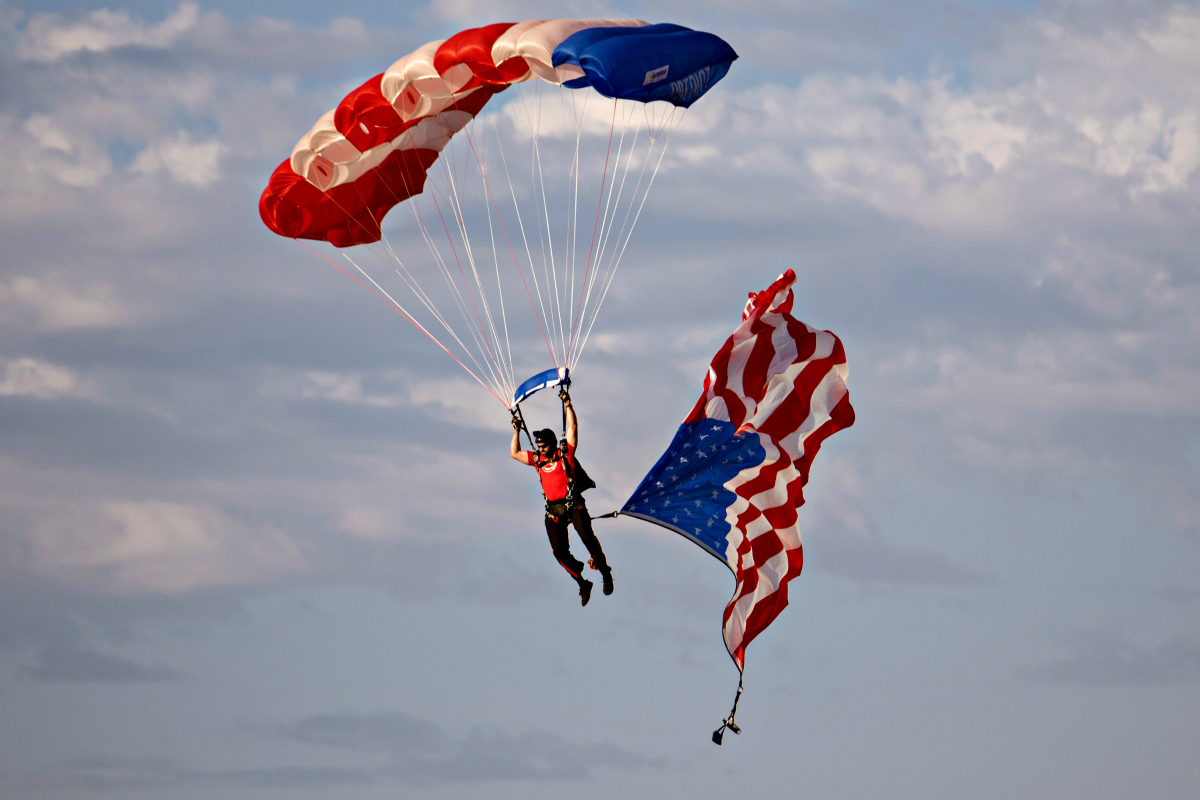 A former Navy SEAL with the Patriot Parachute Team descends onto the field waving a large American flag.