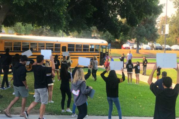 Cheerleaders, ASB leaders and others greet an arriving school bus
