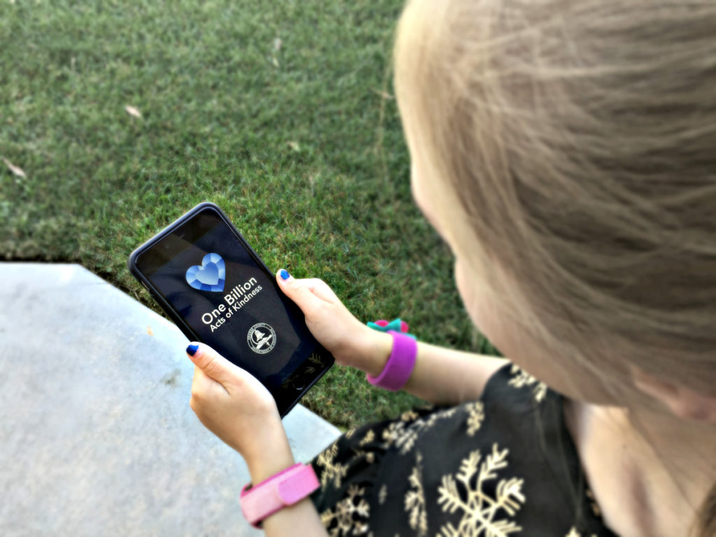 Girl holding iPhone with kindness app