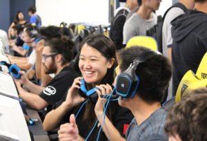 students smiling while sitting at a row of computers playing an online video game