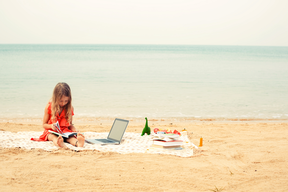 An image of a girl reading at the beach