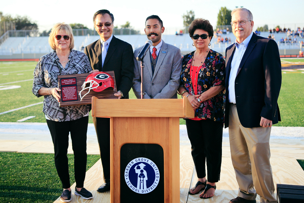 Sally Monsoor, Michael's mother, is presented with a mounted football helmet signed by Michael's former teammates at Garden Grove High School