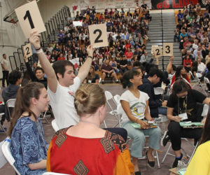 A student on an Academic decathlon team holds up two numbers indicating his team answered a question correctly