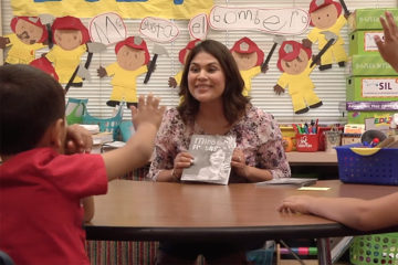 female teachers shows two students a book