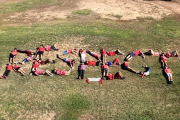"Students lying in a field, spelling out ""RESPECT."""