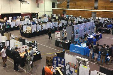 Booths inside Chapman University gym display students' ocMaker Challenge projects