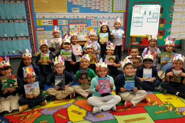 students in a classroom each hold up donated books