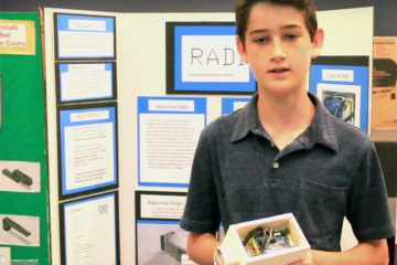 A student holds his project during the ocMaker Challenge