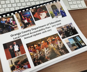 A hard copy of Orange County Department of Education's Local Control Accountability Plan sits on a desk.
