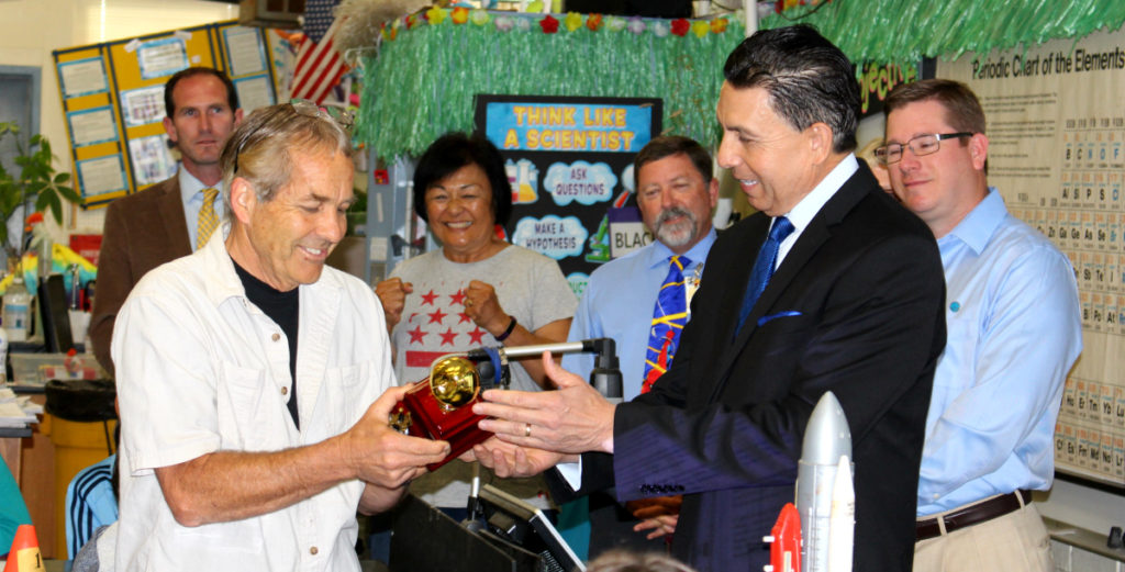 Superintendent Al Mijares passes a Golden Apple award to Jim Blackie of Ensign Intermediate School