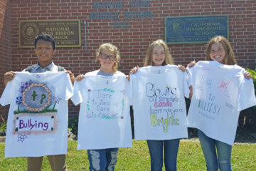 Students from Marine View hold up t-shirts with anti-bullying messages they created