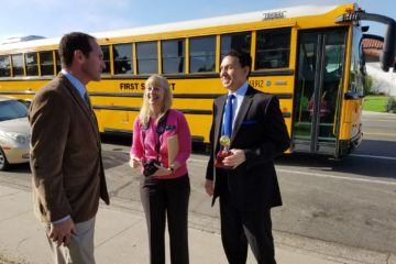 Orange County Superintendent of Schools Dr. Al Mijares and others in front of a school bus