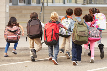 A group of students run toward their elementary school