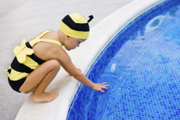 Girl in bee swimsuit next to pool
