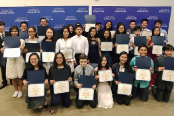 a roup of students hold up certificates they received from a law school program